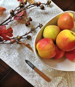 apples in bowl with branch and peeler
