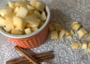 chopped apples in cup with cinnamon sticks