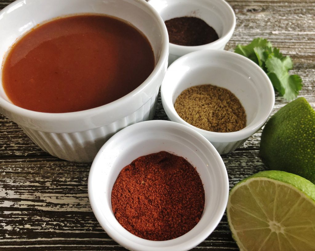 Enchilada sauce and spices in white ramekins