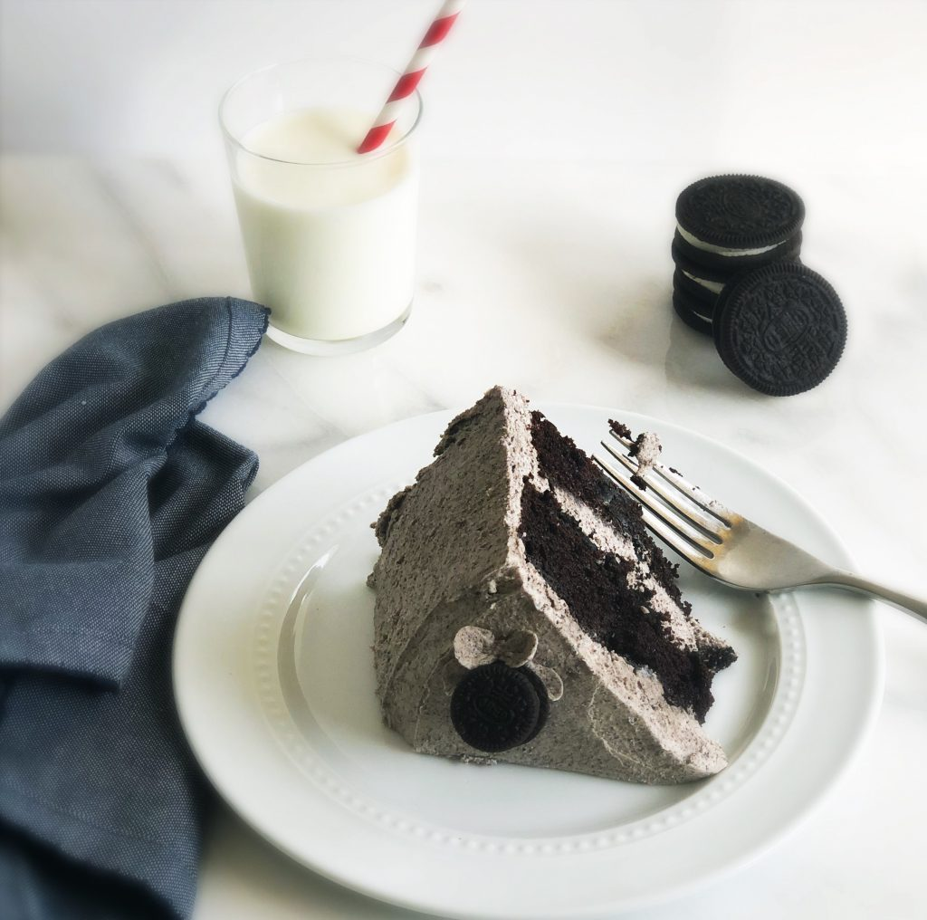slice of oreo cake with fork and glass of milk