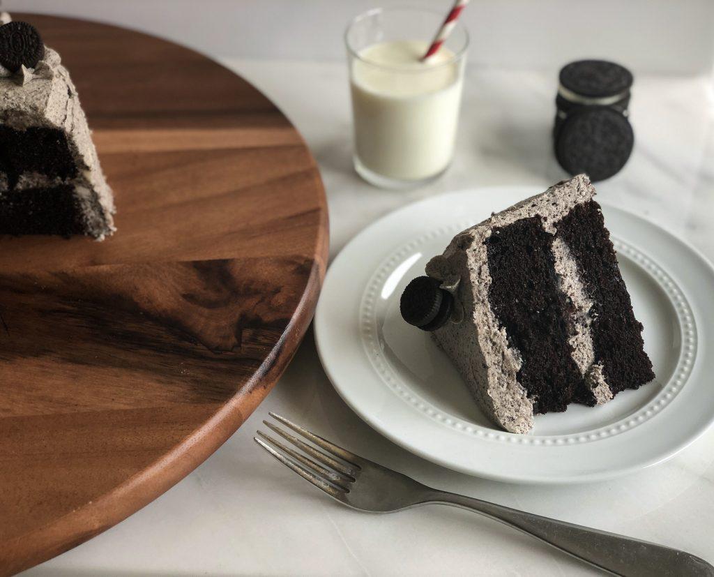 slice of oreo cake with whole cake, milk and oreos