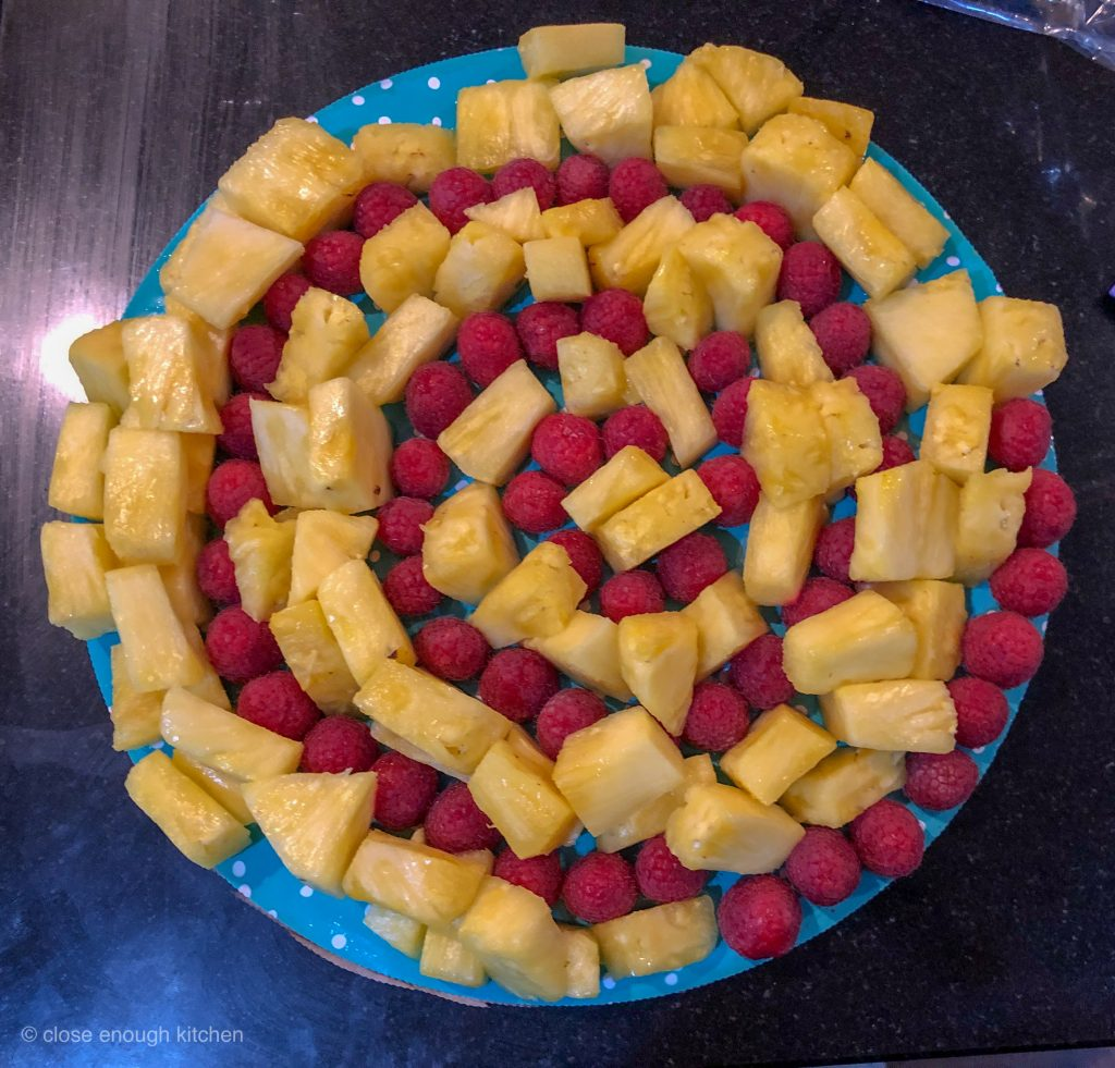 Plate of pineapple and raspberries